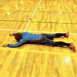 木製の床の上に横たわる人 - No.854028