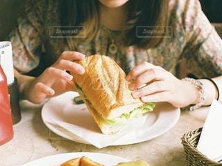 サンドイッチを食べるテーブルに座っている女性の写真・画像素材[909251]