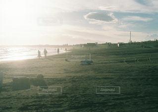 水の体の横にあるフィールドで人々 のグループの写真・画像素材[1339736]
