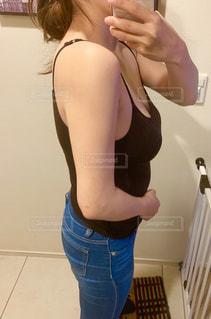 カメラにポーズ鏡の前に立っている女性の写真・画像素材[2083775]