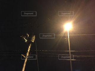 夜の闇に浮かび上がる街灯の光を見上げるの写真・画像素材[803205]
