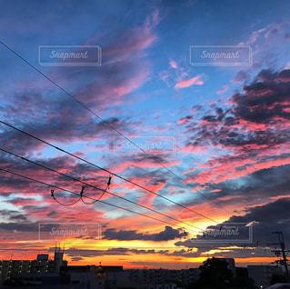 夕焼け空に浮かぶ雲のグループの写真・画像素材[705582]