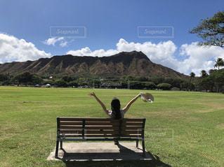 緑豊かな野原の上に座っている空の公園のベンチの写真・画像素材[2127762]