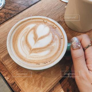 木製のテーブルの上のコーヒーカップとラテの写真・画像素材[1173656]