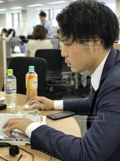 ノートパソコンを使用してテーブルに座っている男の人の写真・画像素材[754182]
