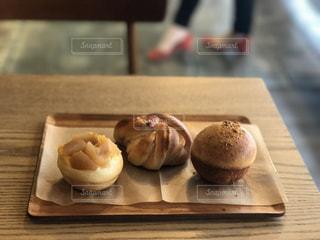 木製のテーブルの上に食べ物の写真・画像素材[1090382]