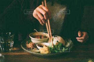 食べ物の皿を持ってテーブルに座っている人の写真・画像素材[2370541]