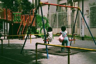 遊び場の後ろに乗っている人の写真・画像素材[2370580]