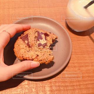 皿の上のクッキーを持っている手 - No.1049687