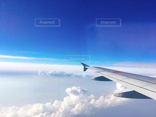 曇りの青い空を飛んでいるジェット大型旅客機の写真・画像素材[1165619]