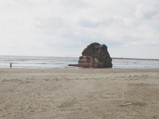 バック グラウンドでの干し草の山の岩のビーチの人々 のグループの写真・画像素材[1118738]