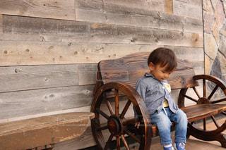 木製のベンチに座っている少年の写真・画像素材[1142929]