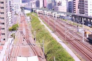 バック グラウンドで高線と市内でトラックに大きな長い列車の写真・画像素材[1164385]
