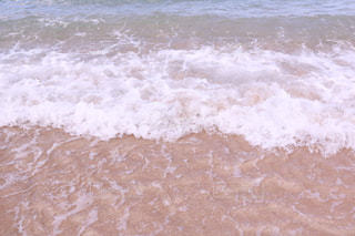 砂浜の上に波に乗っている人の写真・画像素材[1233998]