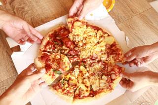 まな板の上のピザのスライスを持っている手の写真・画像素材[1318743]