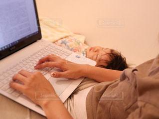 少年がベッドの上に座っているラップトップ コンピューターを使用しての写真・画像素材[1440893]