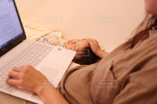 ベッドの上に座っているラップトップ コンピューターを使用している人の写真・画像素材[1440894]