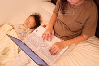 本を読んでベッドで横になっている人の写真・画像素材[1440896]
