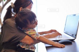 テーブルの上に座っているラップトップ コンピューターを使用して子の写真・画像素材[1441669]