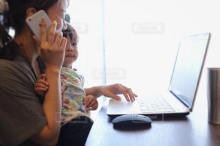 ラップトップ コンピューターを使用してテーブルに座っている人々 のグループの写真・画像素材[1441671]