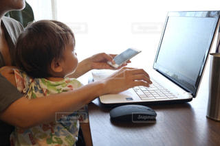 ラップトップ コンピューターを使用してテーブルに座っている赤ちゃんの写真・画像素材[1441672]