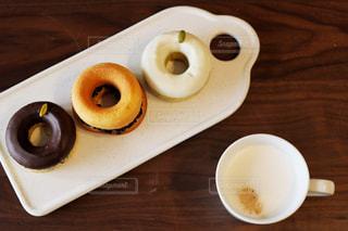一杯のコーヒーとドーナツの木製テーブルの上に座っています。の写真・画像素材[1441970]