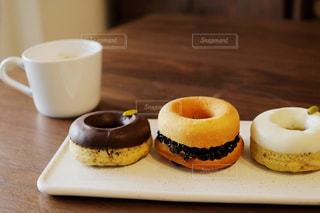 近くのコーヒー カップの横に座っているドーナツのアップの写真・画像素材[1441972]