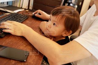 木製テーブルの上に座っているラップトップ コンピューターを使用して若い男の子の写真・画像素材[1476035]