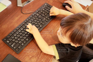 木製テーブルの上に座っているラップトップ コンピューターを使用して若い男の子の写真・画像素材[1476037]