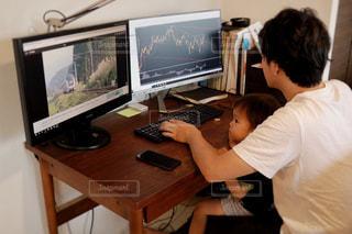 テーブルの上に座っているラップトップ コンピューターを使用して若い男の子の写真・画像素材[1476039]