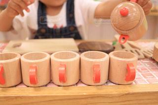 コーヒーのカップをテーブルに座っている少女の写真・画像素材[1517258]