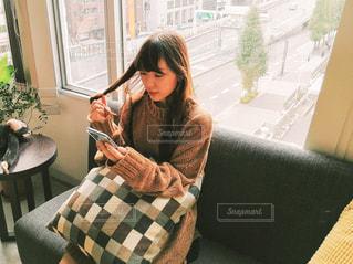 窓の前のテーブルに座っている女性の写真・画像素材[1585816]