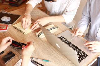 ラップトップを使用してテーブルに座っている人々 のグループの写真・画像素材[1633131]