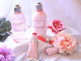 テーブルの上の花の花瓶の横にあるボトルの写真・画像素材[1633455]