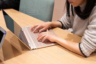 ラップトップ コンピューターを使用してテーブルに座っている女性の写真・画像素材[1651096]