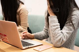 ラップトップ コンピューターを使用してテーブルに座っている女性の写真・画像素材[1651097]