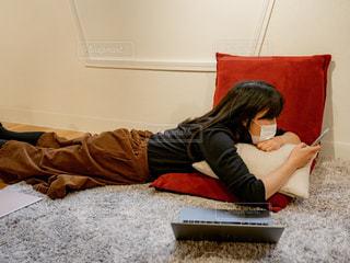 ラップトップを使用してベッドの上で横になっている人の写真・画像素材[1809185]
