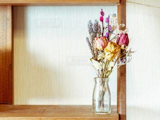 花瓶は、木製のテーブルの上に座っている花でいっぱいの写真・画像素材[1853782]