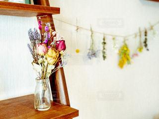 木製テーブルの上に座っている花の花瓶の写真・画像素材[1853790]