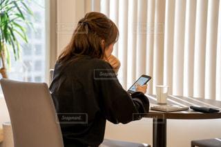 窓の前で机に座っている女性の写真・画像素材[1854097]
