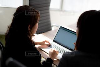 机に座って、ノート パソコンを使用しての人の写真・画像素材[1854100]