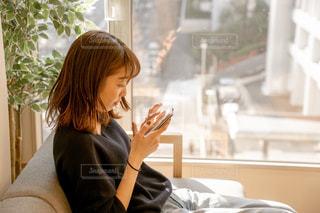 窓の前のテーブルに座っている女性の写真・画像素材[1854106]