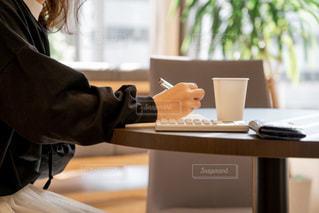 窓の前のテーブルに座っている女性の写真・画像素材[1854113]