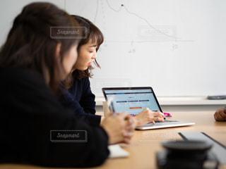 机に座って、ノート パソコンを使用しての女性の写真・画像素材[1854114]