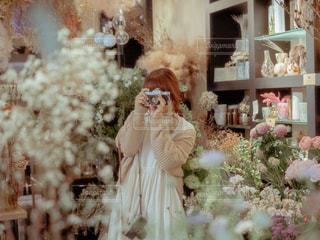 花の前に立っている人の写真・画像素材[1856084]