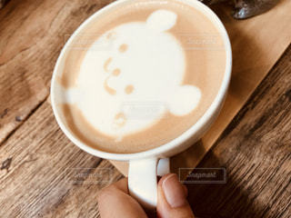 木製テーブルの上のコーヒー カップを持つ手の写真・画像素材[1251395]