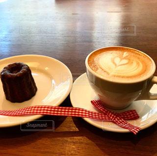 木製のテーブルの上に座っているコーヒーのカップの写真・画像素材[2931858]