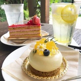 皿の上にケーキを置いたテーブルの上にコーヒーを一杯入れたの写真・画像素材[3473799]