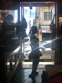 店の窓の前に立っている人の写真・画像素材[935694]