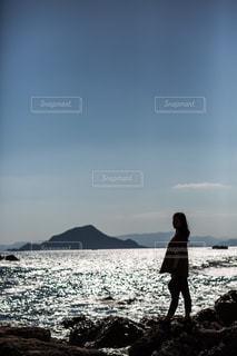 岩のビーチに立っている人の写真・画像素材[1315284]
